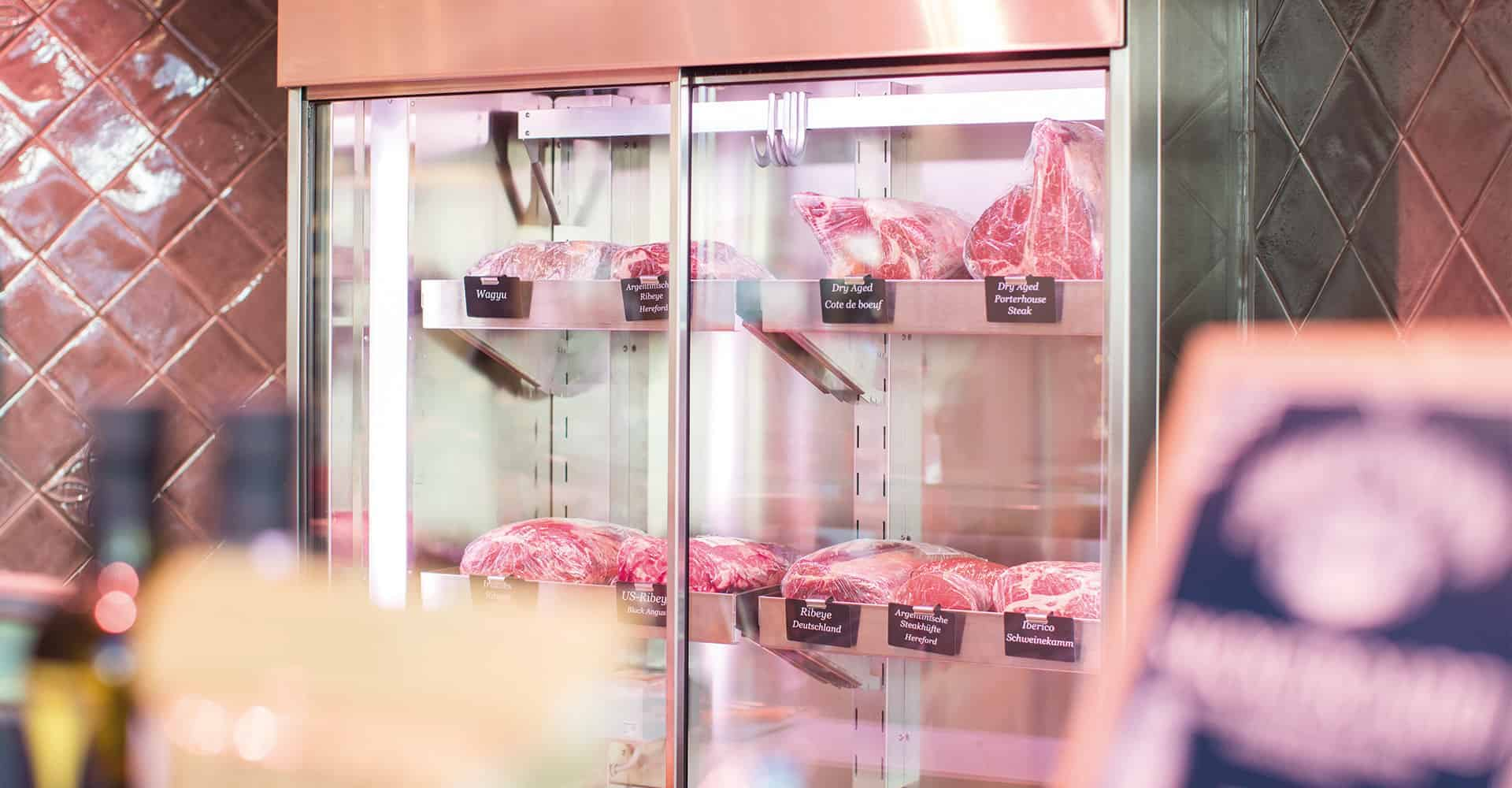 FEINKOST MÜLLER DRESDEN | NEUBAU LADENGESCHÄFT | Das 1940 gegründete Familienunternehmen pflegt seit vier Generationen mit Leidenschaft die Tradition des Fleischerhandwerks. Diese Leidenschaft soll der Kunde beim Kauf spüren. So war es dem Familienunternehmen wichtig, sowohl eine moderne Ladengestaltung umzusetzen als auch das Traditionshandwerk zu darzustellen. Die komplexe Projeksteuerung war unsere größte Herausforderung, über 18 Gewerke mussten gleichzeitg koordiniert werden, damit eine Umsetzung innerhalb von 6 Wochen realisierbar war. Als gestalterisches Highlight sind die Wandfliesen zu benennen, denn jedes Stück Fliese ist handgefertig und somit kompliziert zu verarbeiten. Die Knackerauswahl wird durch ein eigens konzipiertes Raglsystem inszeniert. Der Hackeklotz bekommt eine neue Funktion als Beratungstisch. Ein ausgedienter Fleischwolf wird zu einer Leucht umfunktioniert. Die Neuerstellung des Logos, der Internetseite komplettiert den Relaunch des Corporate Design.